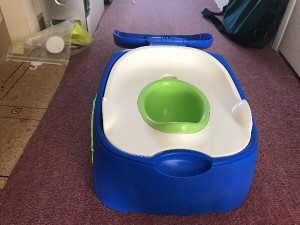 Potty Trainer.  unused toilet trainer for young children. It has a lid that can be used as a step. Side storage for wipes etc. Green centre and white seat removable for washing.