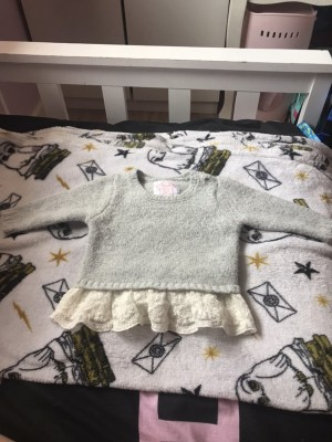 A grey frilly jumper