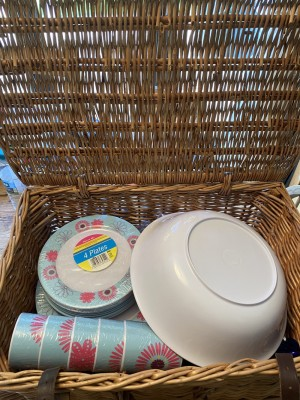 Wicker picnic basket with picnic ware inside it