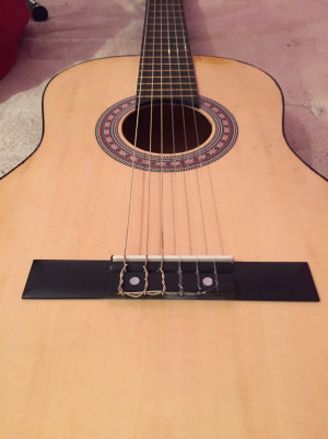 Full size acoustic guitar with a capo and a picks