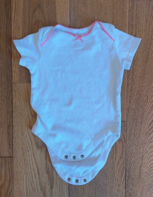 White & pink baby grow